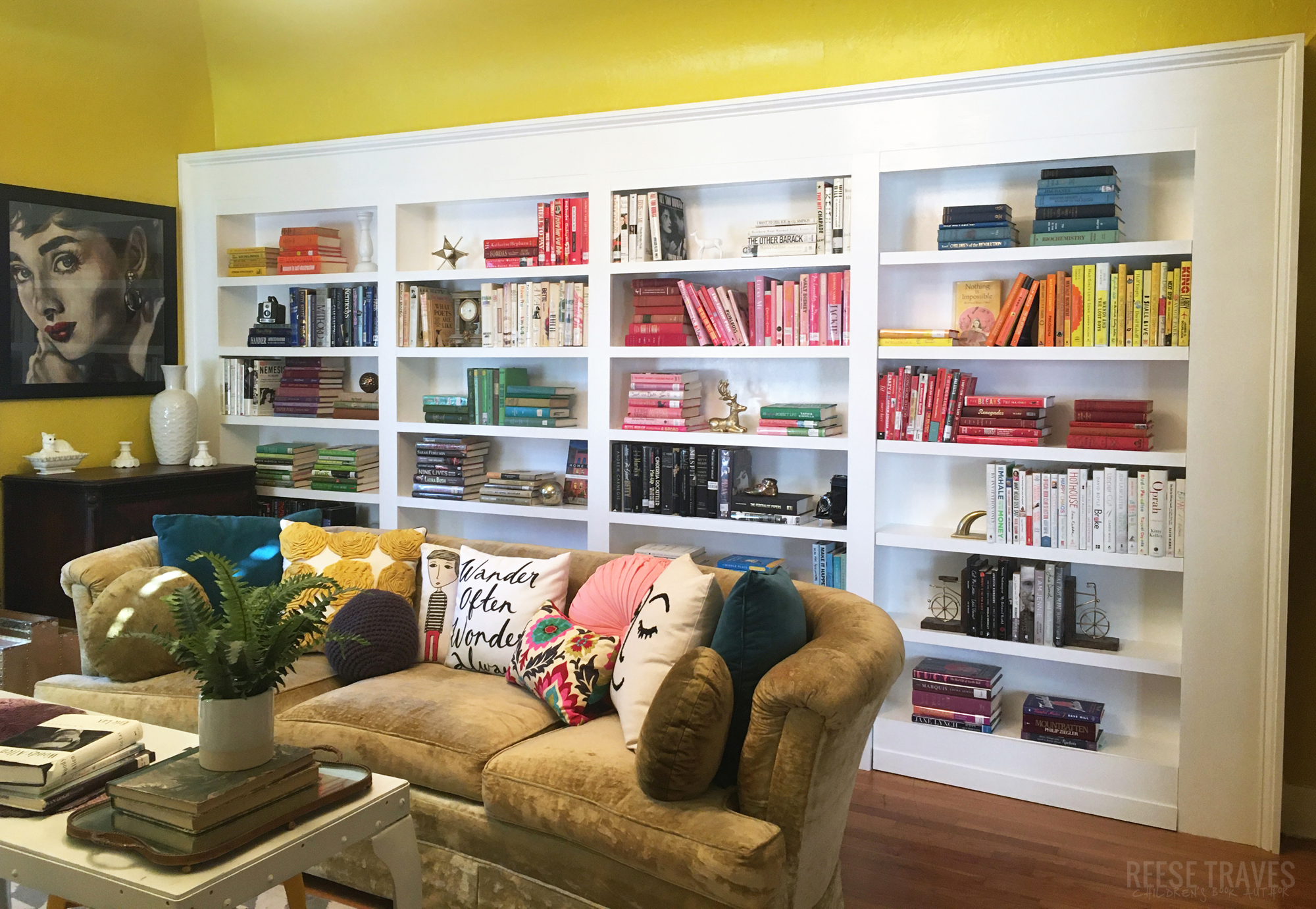 DIY built-in bookshelves with a hidden bookcase door and color blocked book styling. A fun way to add character and book storage to a room!