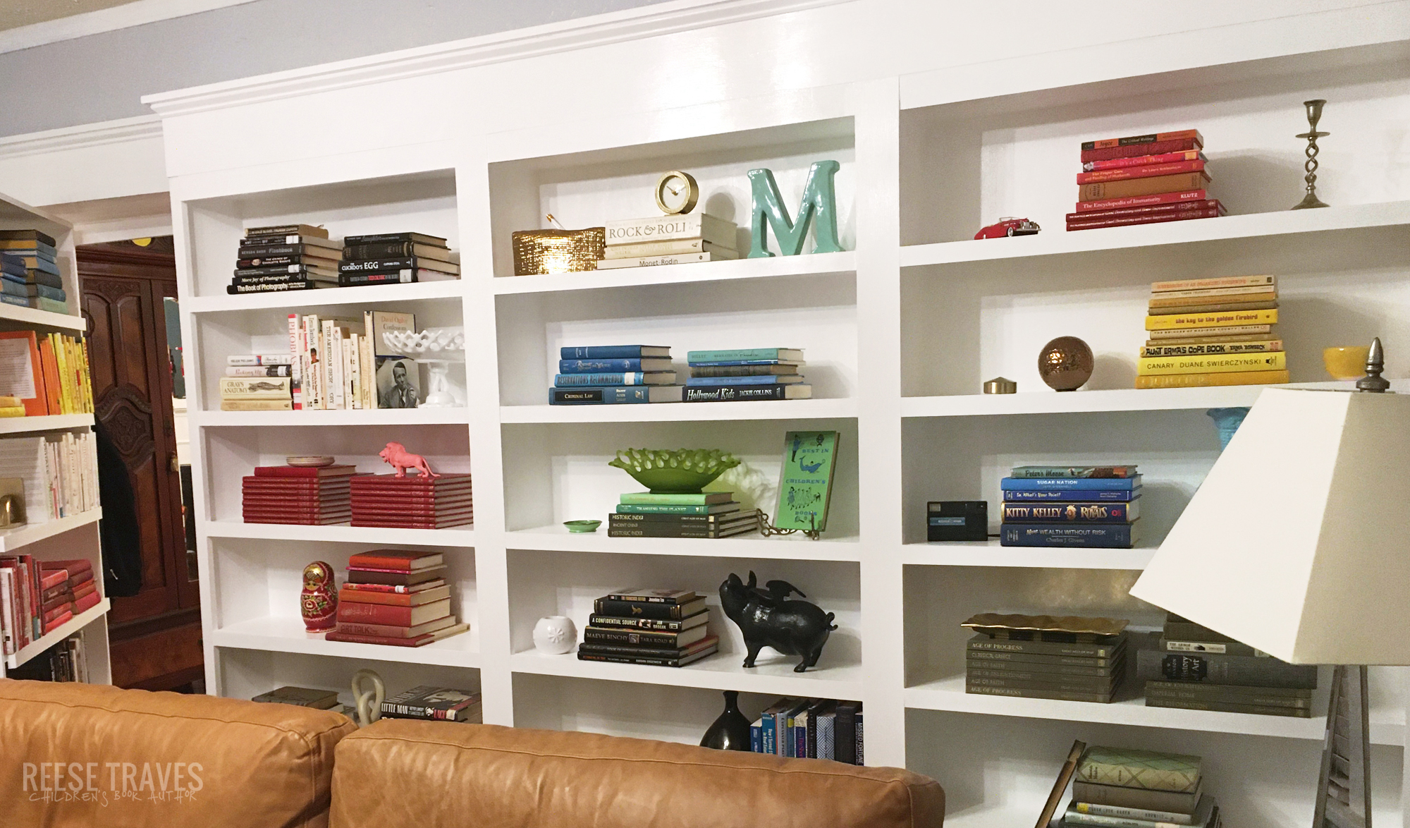 Side 2 of bookshelves with a hidden bookshelf door and rainbow colored books using color blocking bookshelf styling.